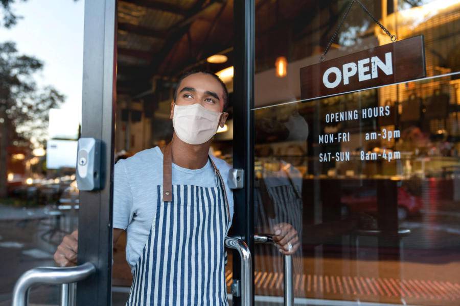 Portrait of a happy waiter opening on the doors at a cafe and smiling